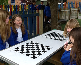 A photo of children at games tables in the playground