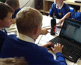 A photo of children using a laptop